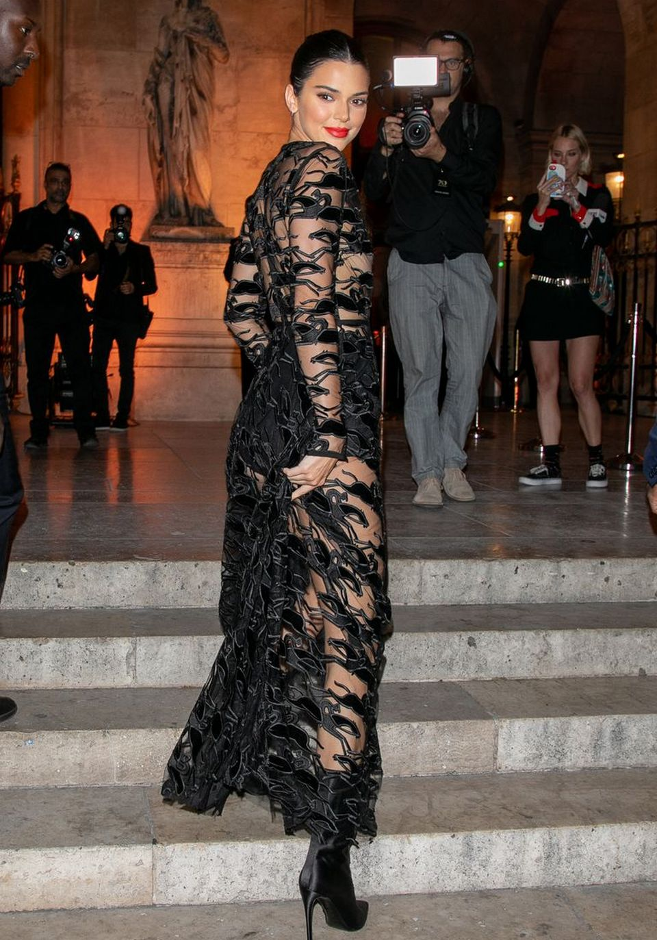 Kendall Jenner looked stunning in a black sheer dress in Paris when she arrived to attend the Longchamp 70th anniversary party at Opera Garnier.