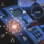 Hand Of Man Using Ip Phone With Flying Icon Of Voip Services And
